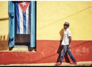 Cuba_Flag_and_Colored_Wall_with_Cuban_Man